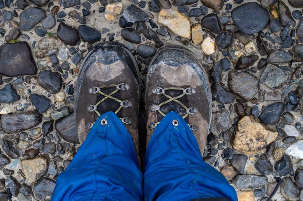 Feet in hiking boots standing on pebbles - Oranj Fitness - Yoga Studio in Fort McMurray
